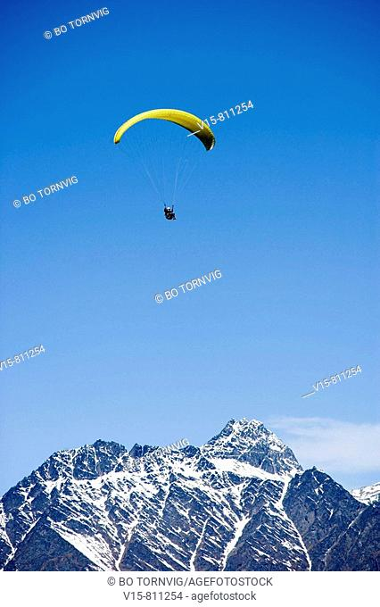 paraglider flying with snow covered mountains in background