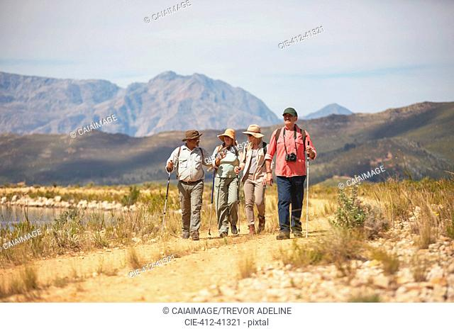 Active senior friends hiking along arid summer landscape