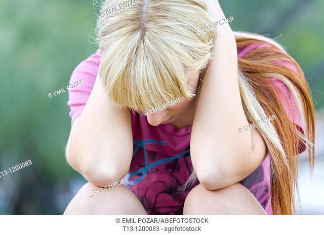 Holding her head between hands depressed young woman