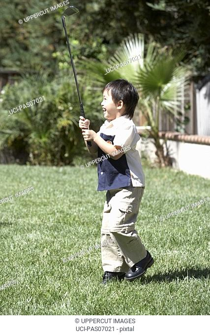 Young boy playing golf on lawn