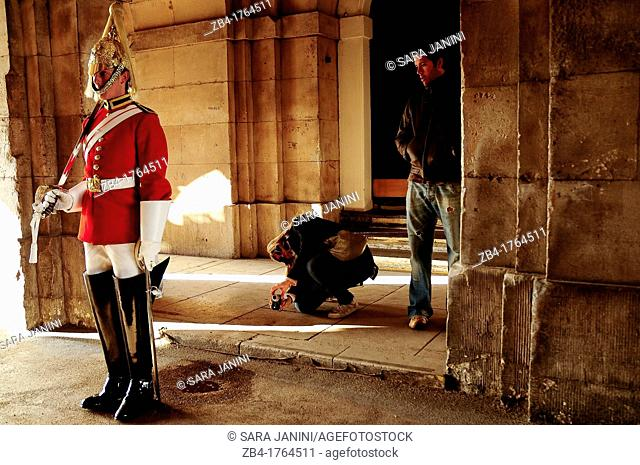 Tourist making photos to a Royal Horse Guard at the tiltyard of the Whitehall Palace, London, England, UK, Europe