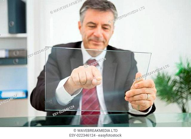 Happy man pointing on his virtual screen on his desk in his office