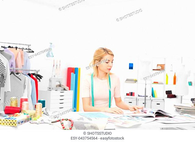 young fashion designer sitting at the desk in her workshop looking throught magazines