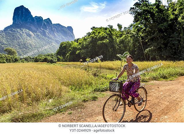 Myanmar (formerly Burma). Kayin State (Karen State). Surrounding Hpa An. Young woman taking a bike ride across field