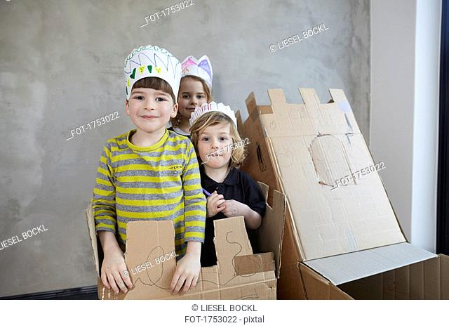 Portrait of friends wearing paper crowns standing with cardboard boxes against wall
