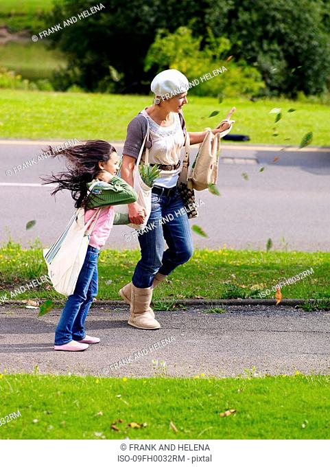 Mother and daughter walking in wind