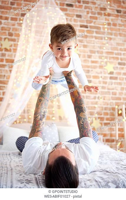 Father lifting up son at Christmas time in bed