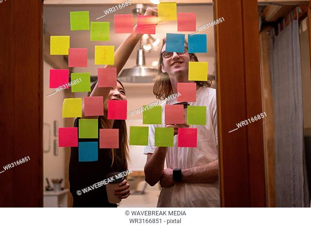 Business colleagues writing on sticky notes