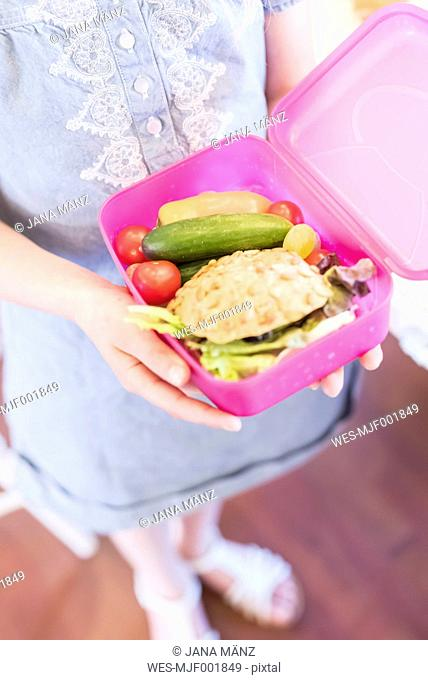 Girl holding lunch box with healthy food