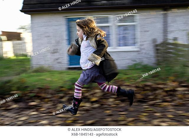 Six year old girl running along residential pavement covered in Autumn leaves