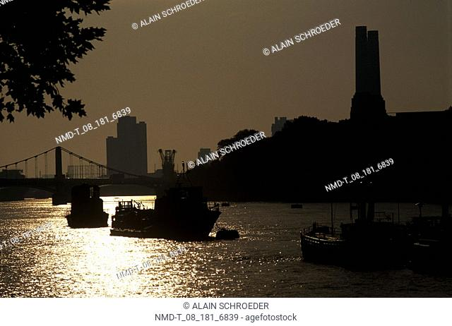 Silhouette of boats in a river at dusk, Chelsea Embankment, London, England