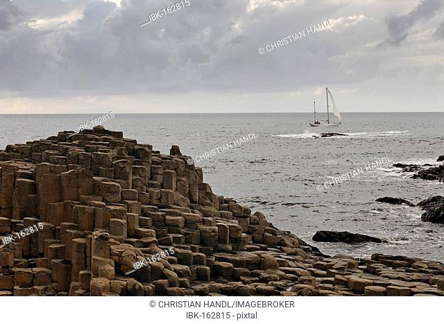 Sailing ship and basalt columns of the Giant's Causeway, Londonderry, North Ireland