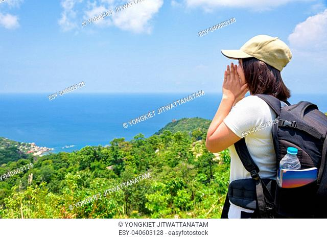 Women tourist with a backpack wear cap raise hand at the mouth yelling and beautiful nature landscape blue sea and sky from high scenic viewpoint at Koh Tao