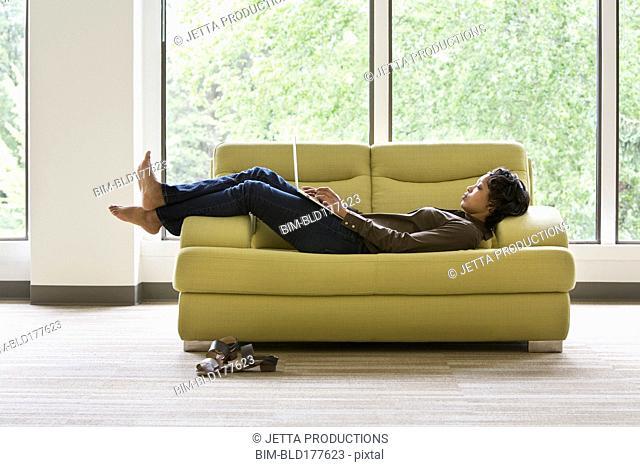 Mixed race businesswoman using laptop on sofa