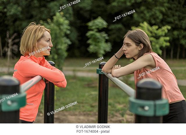 Side view of mother and daughter leaning on railing at park