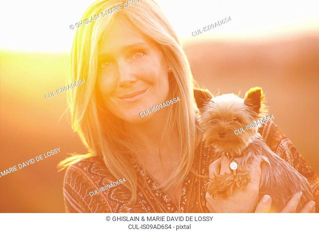 Woman standing in field at dusk holding domestic dog
