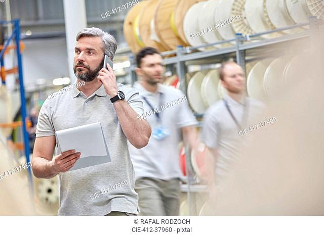 Male supervisor with clipboard talking on ell phone in fiber optics factory