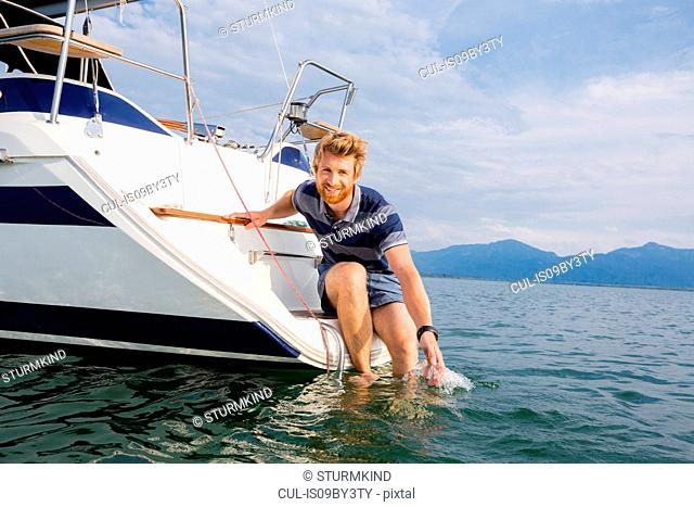 Young man leaning from sailboat on Chiemsee lake, portrait, Bavaria, Germany