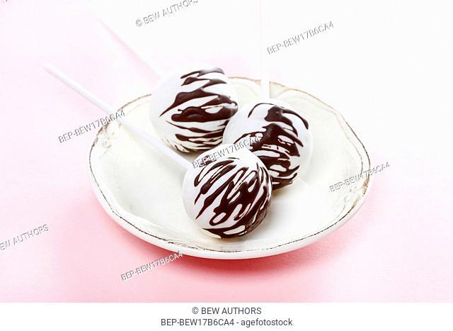 White cake pops decorated with dark chocolate