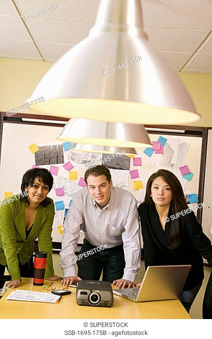 Businessman and two businesswomen leaning on a table in a conference room