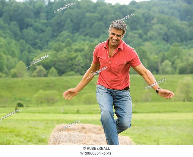 man dancing on a hay bale