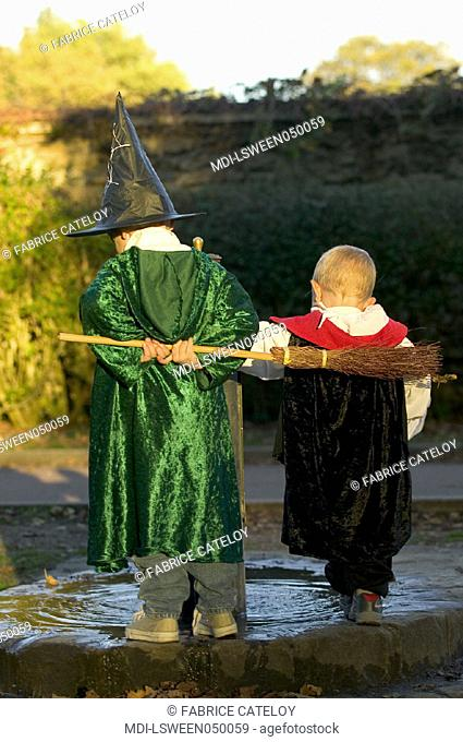 4 and 2 year old boys dressed up as wizards for Halloween and playing with a fountain