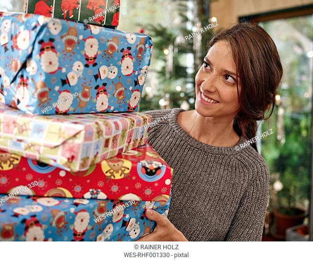 Woman carrying stack of Christmas parcels