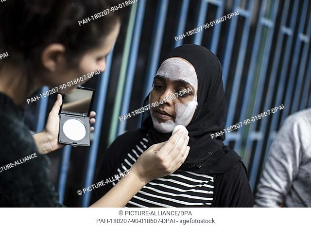 An African asylum seeker gets her face painted in white color, during a protest outside the Rwandan embassy in Herzlia, Tel Aviv, 07 February 2018