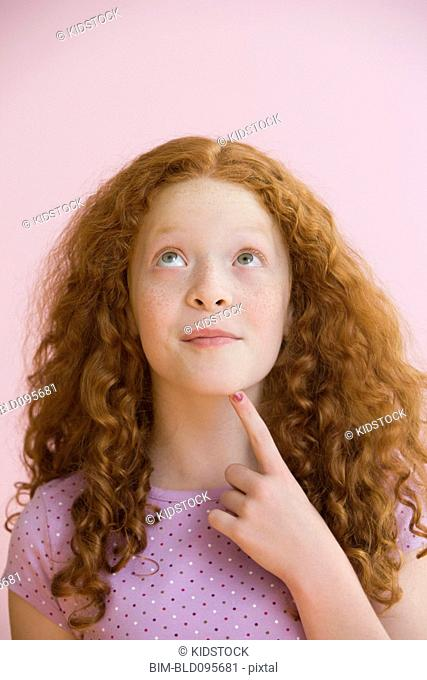 Mixed race girl with red hair, thinking