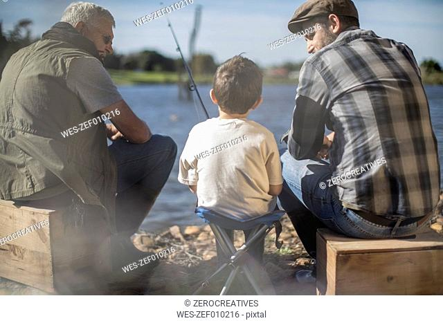 Grandfather, father and son fishing together in a lake