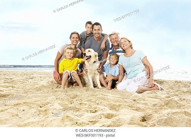 Spain, Portrait of family sitting on beach at Palma de Mallorca, smiling