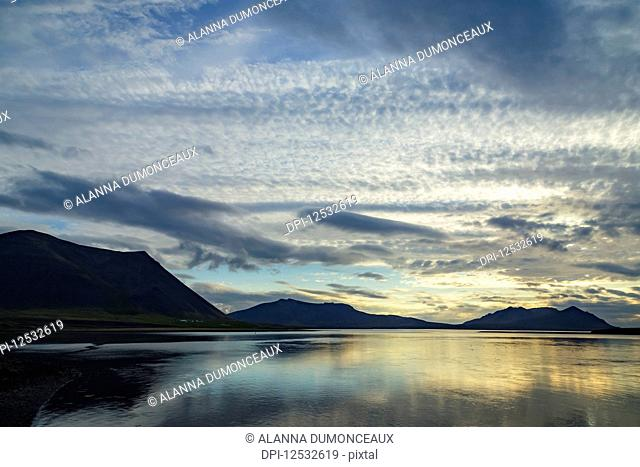 Sunset and cloudy skies over a remote ocean inlet in Western Iceland on the Snaefellsnes Peninsula; Iceland