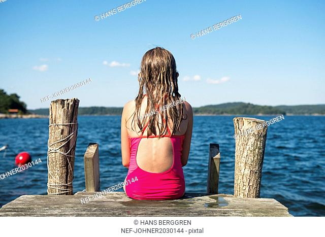 Girl sitting on jetty and looking at sea