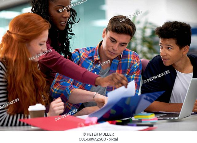 Four young female and male college students teamworking at desk