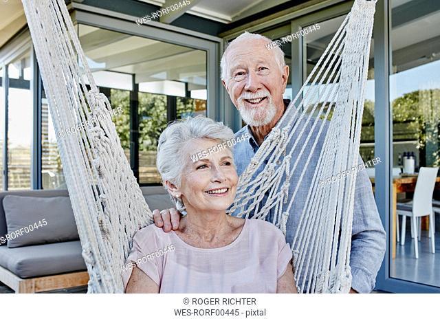 Senior couple on terrace, woman sitting in hammock