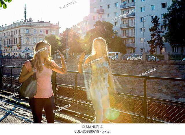 Two adult female friends giving high fiving each other in city, Vienna, Austria