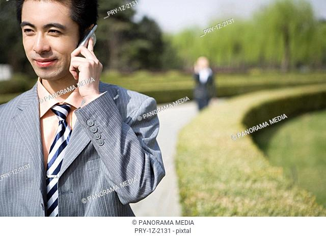 Young businessman using mobile phone, close-up, smiling
