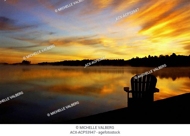 Adirondack chair on cottage deck at sunrise Sharbot Lake, Ontario, Canada