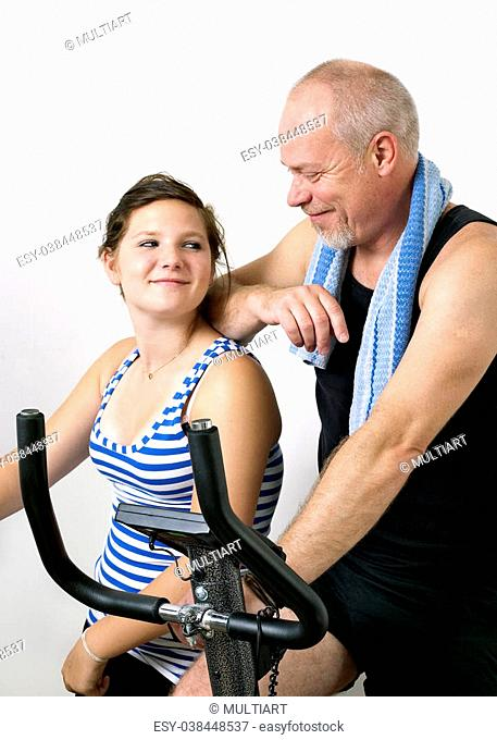 Dad and daughter excercising at home on bicycle