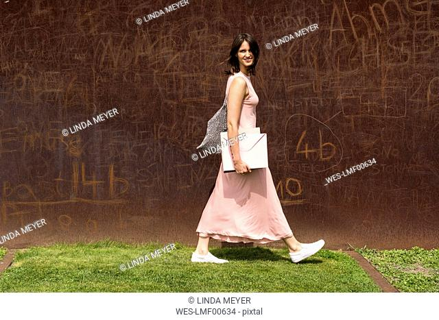 Portrait of young woman in front of corten wall