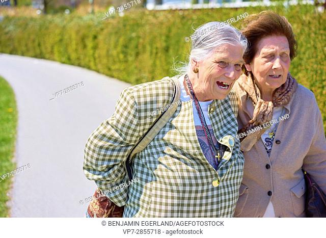 Happy senior woman laughing out loud next to old friend
