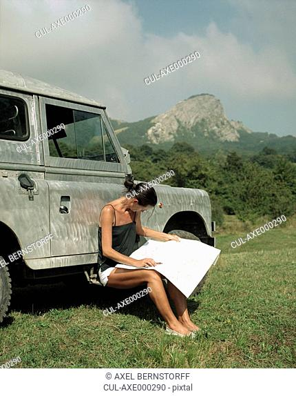 Woman sitting by SUV with a compass and map