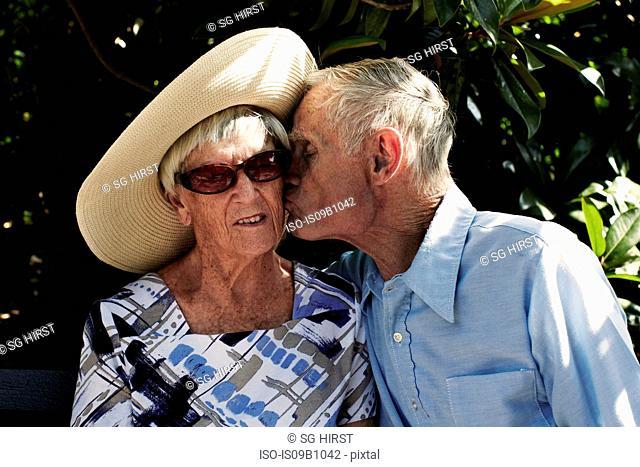 Romantic senior man kissing wife on cheek in park