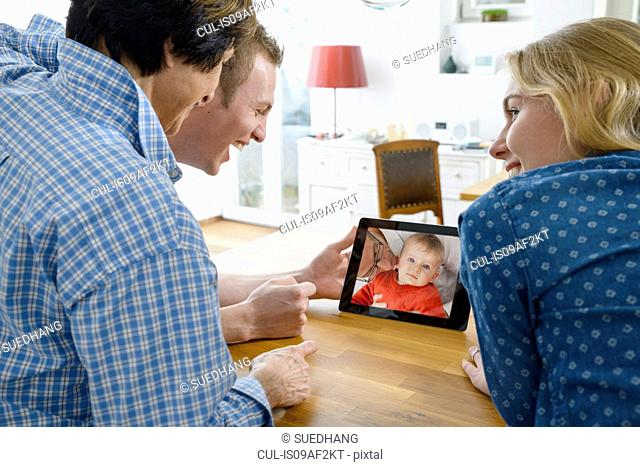 Grandmother and adult grandchildren looking at photo of baby boy on digital tablet