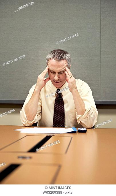 A Caucasian businessman sitting at a desk showing the stress of work