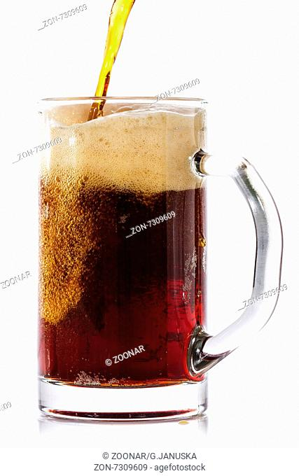 Dark beer pouring into glass. Isolated on white background