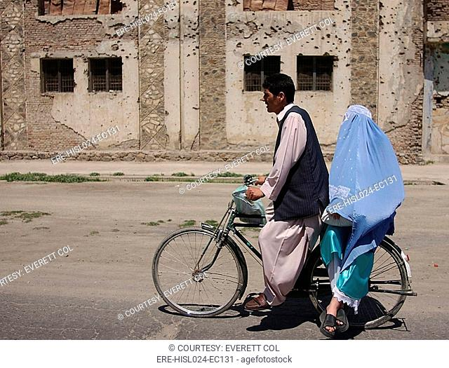 An Afghani couple rides a bicycle through the streets of Kabul Afghanistan after the Taliban were ousted. May 10 2002., Photo by:Everett...