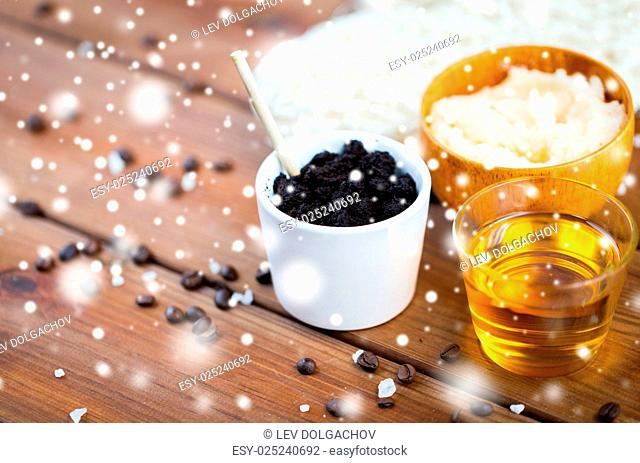beauty, spa, bodycare, bath and natural cosmetics concept - coffee scrub in cup and honey on wooden table over snow