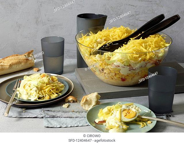 A layered salad with egg and baguette