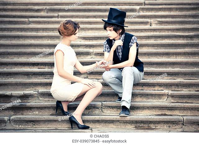 Young elegant couple on a stone stairs